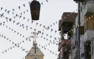 """A cross of an Egyptian Coptic Orthodox church is seen under a """"Fanous"""" decorated lantern in the town of Nagaa Hamady, in Qena, 700 km (435 miles) south of Cairo, January 9, 2010. REUTERS/Asmaa Waguih"""