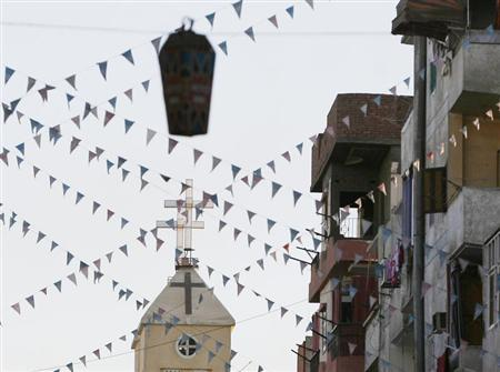"A cross of an Egyptian Coptic Orthodox church is seen under a ""Fanous"" decorated lantern in the town of Nagaa Hamady, in Qena, 700 km (435 miles) south of Cairo, January 9, 2010. REUTERS/Asmaa Waguih"