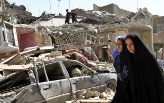 epa04833859 Iraqis walk past a house destroyed by an Iraqi airforce bombing in the Nairiyah district, eastern Baghdad, Iraq, 6 July 2015. According to Iraqi officials a plane belonging to the Iraqi airforce accidentally dropped a bomb on a part of Baghdad, due to a technial failure, killing at least seven.  EPA/ALI ABBAS