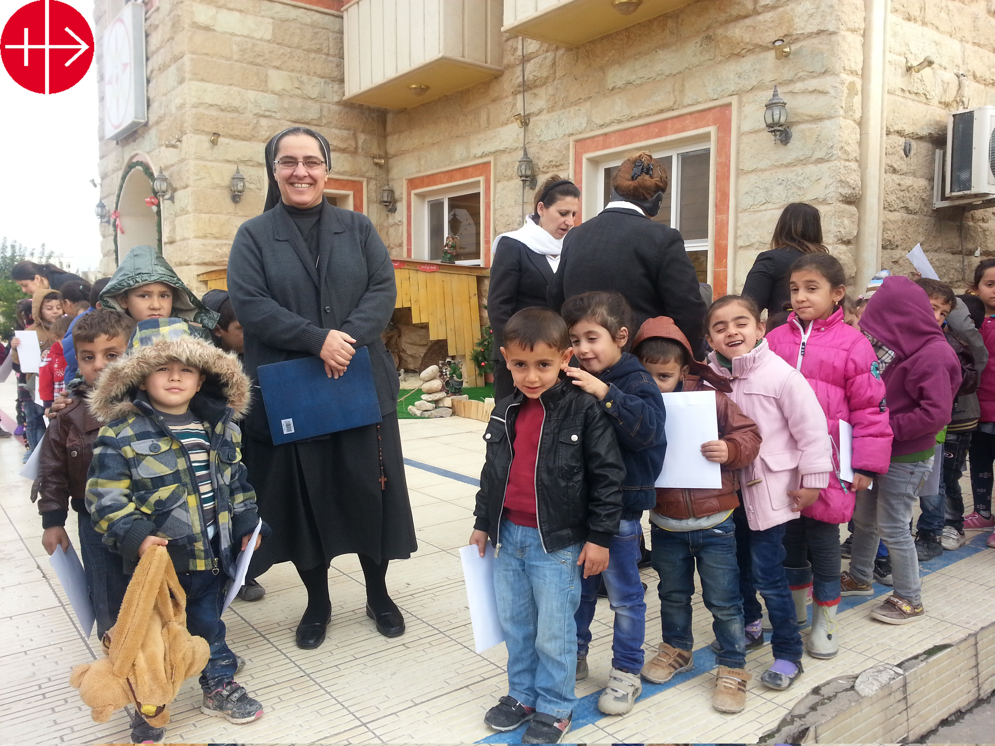 Sister Sanaa Hana is the superior od the Sisters of the Sacred Hart. Their convent in Mossul was destroyed by ISIS. Before the sisters had to flee the City and leave everything behind. The Picture shows Sister Sanaa in Erbil with children in front of a house of the congregation where she found refuge. IRAQ / NATIONAL 14/00254 Existential aid for 20 displaced Sacred Heart sisters from Mosul, 2014/ 2015