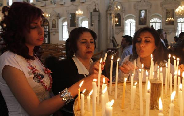 epa03183560 Syrian Orthodox Christians lit candles at the Maryamiyeh Chruch in Damascus, Syria, 15 April 2012. Orthodox Christians celebrate Easter several weeks after observances by other Christian denominations. Christians pose around 8 percent of Syria's 23 millions Sunni-majority inhabitants.  EPA/YOUSSEF BADAWI
