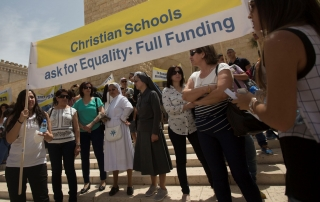 In this photo taken Wednesday, May 27, 2015, Arab Israeli Christians hold signs during a demonstration in front of the education ministry in Jerusalem. Private Christian schools are among Israel's highest ranked educational institutions, established by churches in the Holy Land hundreds of years ago long before Israel was established. But school administrators are accusing Israel of slashing their funding as a pressure tactic to get them join the Israeli public school system a move they say would interfere with the schools' Christian values and high academic achievements. (AP Photo/Sebastian Scheiner)
