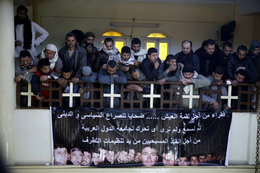 """A man mourns over Egyptian Coptic Christians who were captured in Libya and killed by militants affiliated with the Islamic State group, inside the Virgin Mary Church in the village of el-Aour, near Minya, 220 kilometers (135 miles) south of Cairo, Egypt, Monday, Feb. 16, 2015. Egyptian warplanes struck Islamic State targets in Libya on Monday in swift retribution for the extremists' beheading of a group of Egyptian Christian hostages on a beach, shown in a grisly online video released hours earlier. The banner in Arabic reads, """"poor for a piece of bread.. Victims of political and religious conflict, we did not hear nor see any reactions from Arab nations to save the lives of these Christians from the hands of extremists. """" (AP Photo/Hassan Ammar)"""