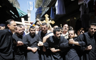 Christian worshippers lock arms during a procession along the Via Dolorosa on Good Friday during Holy Week in Jerusalem's Old City April 18, 2014. Christian worshippers on Friday retraced the route Jesus took along Via Dolorosa to his crucifixion in the Church of the Holy Sepulchre. Holy Week is celebrated in many Christian traditions during the week before Easter. REUTERS/Ammar Awad (JERUSALEM - Tags: RELIGION TPX IMAGES OF THE DAY) - RTR3LTO5