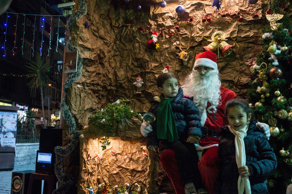 Children pose for a photograph together with a man dressed as Santa Clause during Christmas celebrations in Damascus.