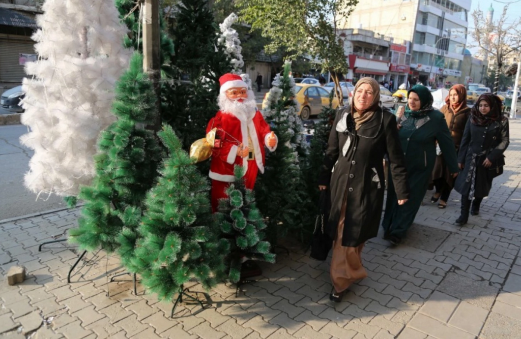Iraqis pass by a shop selling Christmas decorations in the Karrada neighborhood of Baghdad on Thursday. (Karim Kadim/AP)