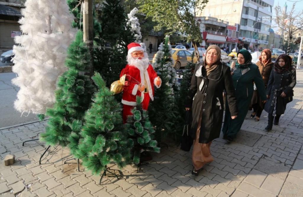 Iraqis pass by a shop selling Christmas decorations in the Karrada neighborhood of Baghdad on Thursday. (Karim Kadim/AP)