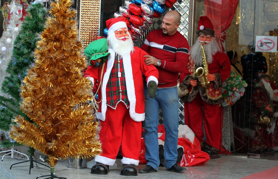 An Iraqi man displays a Santa Claus outside a shop in Baghdad's Karrada district ahead of Christmas. (Ahmad al-Rubaye/AFP)