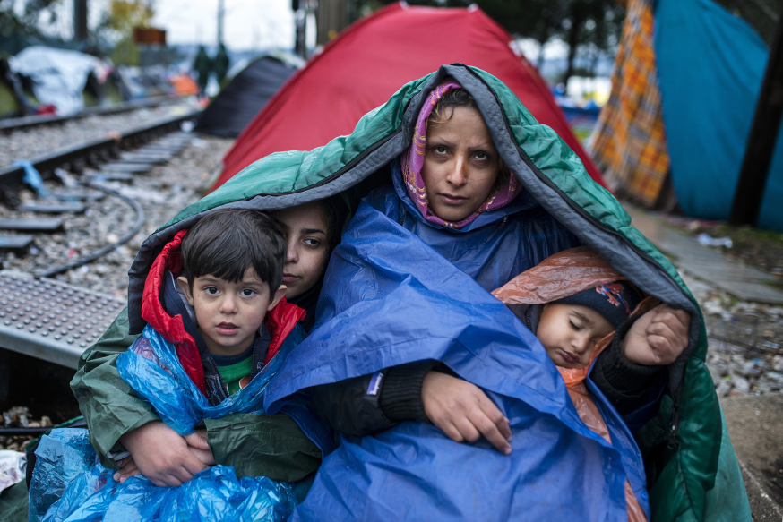 TOPSHOTS A woman and her children look on as migrants and refugees wait to cross the Greece-Macedonia border in the rain on November 27, 2015 near Gevgelija. Over 200 migrants on November 26 tried to break through barbed wire fences to cross from Greece into Macedonia, which imposed new border restrictions last week, throwing stones at police, AFP reporters said. Since last week, Macedonia, which lies on the main migrant route to northern Europe, has restricted passage to only Syrians, Iraqis and Afghans who are considered war refugees. All other nationalities are deemed economic migrants and told to turn back. AFP PHOTO / ROBERT ATANASOVSKI / AFP / ROBERT ATANASOVSKI