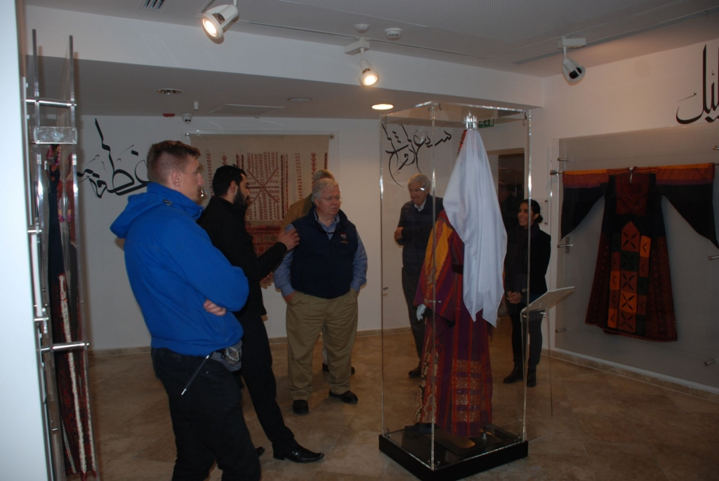 """UNICEF Delegation listening to the story of the traditional wedding dress of Bethlehem, the head dress """"Al-Shatweh"""" worn by married women, and the chest piece indicating the dresser's religion – January 20th, 2016"""