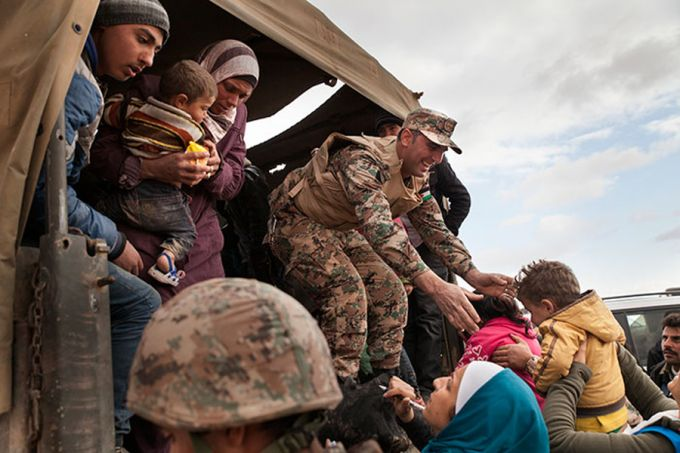 Jordanian_troops_and_UNHCR_members_help_bring_refugees_to_the_Zaatari_refugee_camp_Lucian_Perkins_for_the_US_Holocaust_Memorial_Museum_CNA_8_17_15