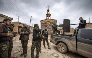 Fighters of the Kurdish People's Protection Units (YPG) stand near a pick-up truck mounted with an anti-aircraft weapon in front of a church in the Assyrian village of Tel Jumaa, north of Tel Tamr town February 25, 2015. Kurdish militia pressed an offensive against Islamic State in northeast Syria on Wednesday, cutting one of its supply lines from Iraq, as fears mounted for dozens of Christians abducted by the hardline group. The Assyrian Christians were taken from villages near the town of Tel Tamr, some 20 km (12 miles) to the northwest of the city of Hasaka. There has been no word on their fate. There have been conflicting reports on where the Christians had been taken. REUTERS/Rodi Said (SYRIA - Tags: POLITICS CIVIL UNREST CONFLICT RELIGION TPX IMAGES OF THE DAY)