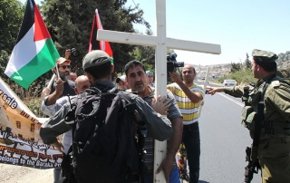 Palestinian, Israeli and Christian foreign activists confront Israeli soldiers as they walk toward Beit al-Baraka, a church compound, situated between the Al-Arub refugee camp and the city of Hebron in the occupied West Bank during a demonstration condemning the Israeli occupation, Aug. 15, 2015.  (photo by Getty Images/Hazem Bader)