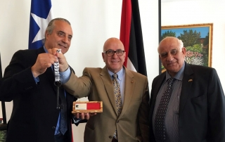 "Sir Rateb Rabie presents ""Key of Palestine,"" to Arab Center President, Alex Cattan. From left to right: Alex Cattan, Sir Rateb Rabie, and Antonio Hanania Batshon."