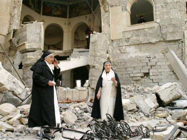 Two Dominican Sisters survey the damage on a church in Iraq following an ISIS attack.