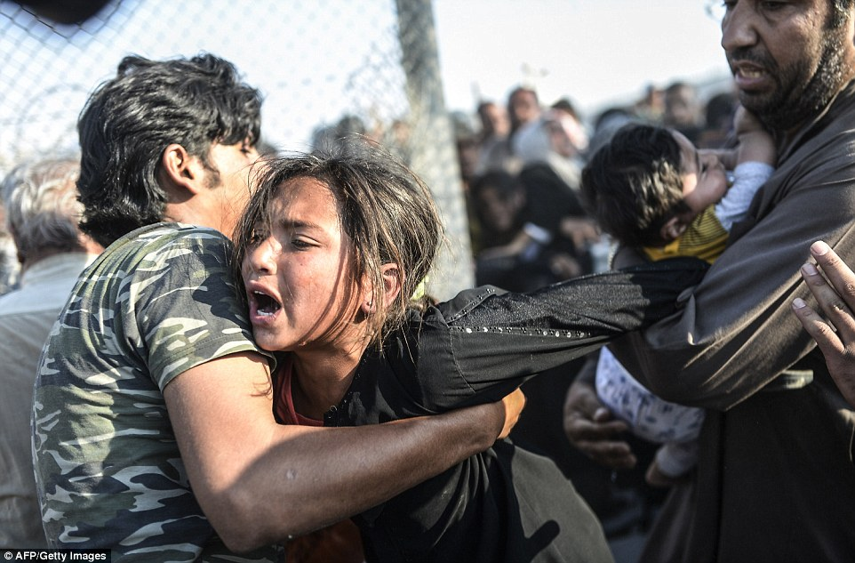 Syrian refugees attempt to break through a barbed wire fence in a desperate bid to flee from the ISIS-held border town of Tal Abyad and cross into Turkey. Photo Credit: AFP/Getty Images