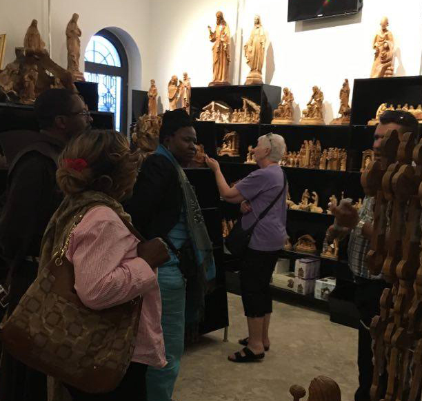 Pilgrims admire the olivewood handcrafts made by Palestinian Christians in the Holy Land.