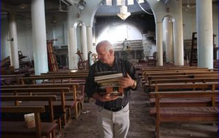 Khalid Yaako Touma, a school teacher and deacon in the village of Karamlesh, collects religious books from one of the churches in the village that ISIS destroyed. ( Alice Fordham/NPR)