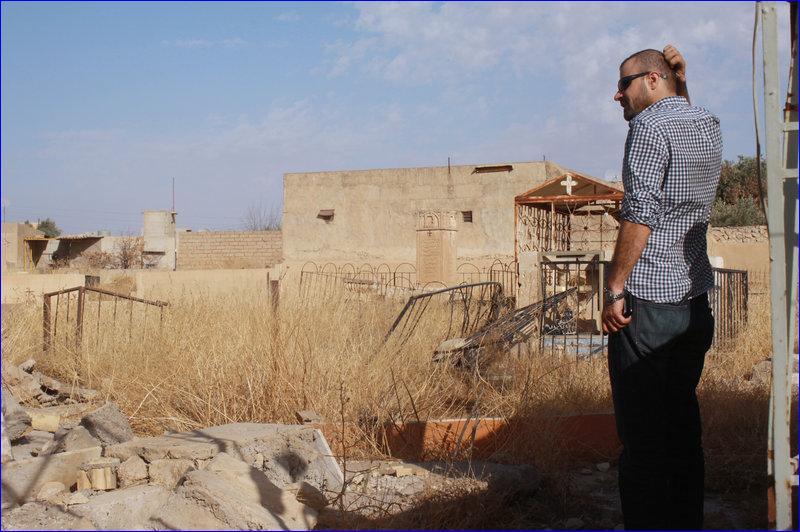 aher Bahoo stands in a damaged graveyard in his home village of Karamlesh. ( Alice Fordham/NPR)
