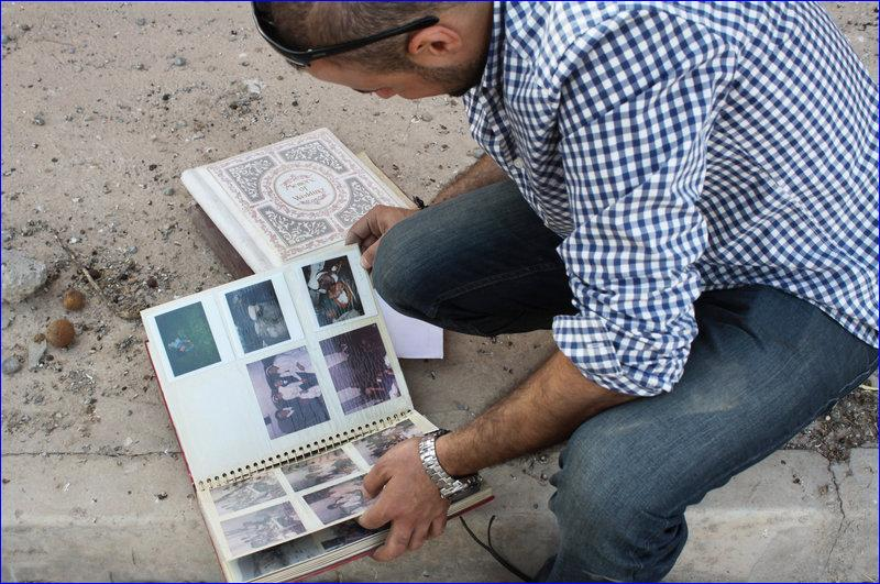 Businessman Taher Bahoo lingers over family photo albums he salvaged from his home, which was ransacked by ISIS. ( Alice Fordham/NPR)